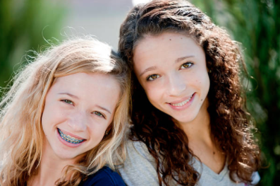 Two girls smiling with braces